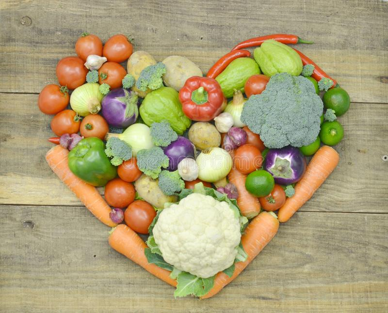 Heart made fresh vegetable on wooden; closeup stock image