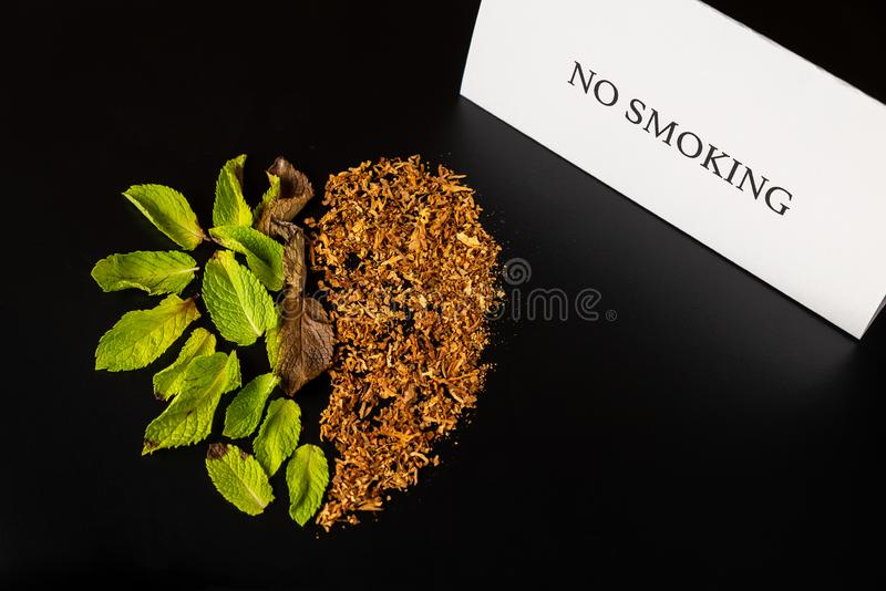 Heart made from green plant/mint and tobacco is on the black table/background. There are note `No Smoking`. No Smoking Day. No Tob. Acco Day stock image