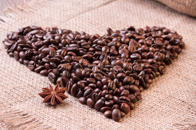 Heart made out of coffee beans on textural background stock photo