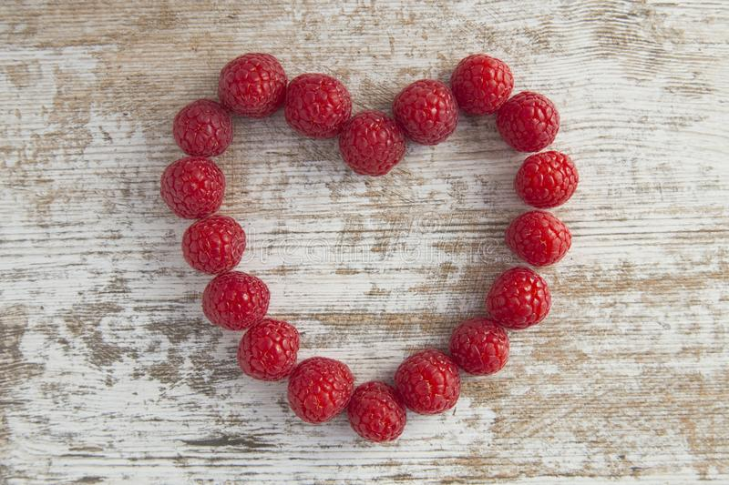 Heart made out of raspberries over white wooden background stock photos