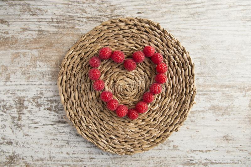 Heart made of raspberries on rustic background royalty free stock photography