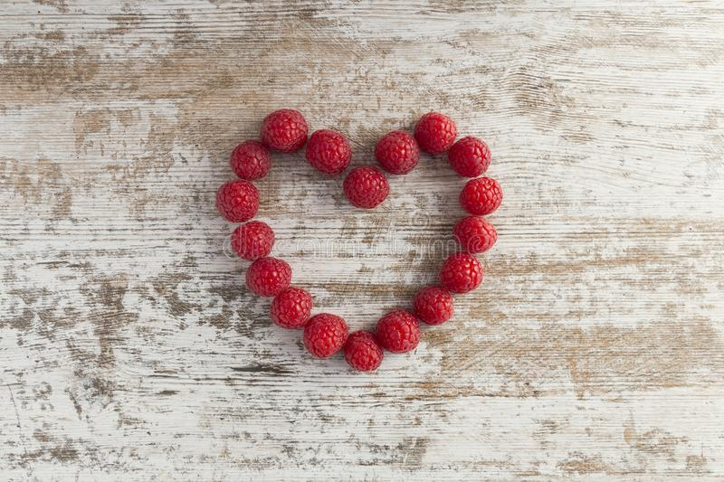 Heart made of raspberries on white wooden background. royalty free stock images