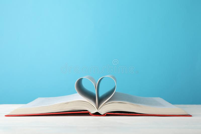 Heart made of pages. Book against blue background stock photo