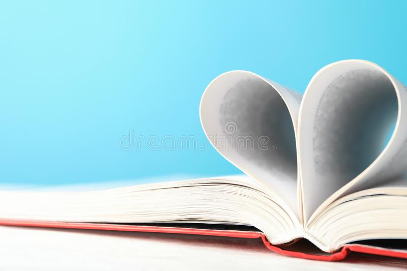 Heart made of pages. Book against blue background. Space for text royalty free stock images