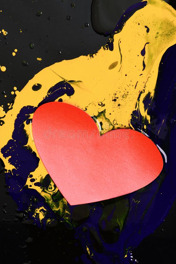 Heart made of paper lying on paints. Drops of paint. Heart made of paper lying on paints. Drops of blue and yellow oil or acrylic paint poured on black stock photo
