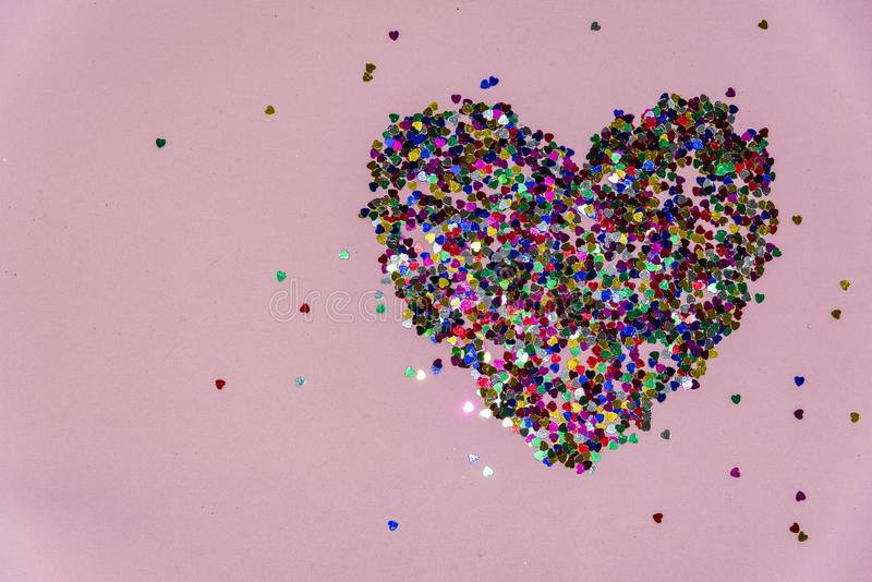 Heart made of plastic confithy hearts on a pink background. abstract stock images