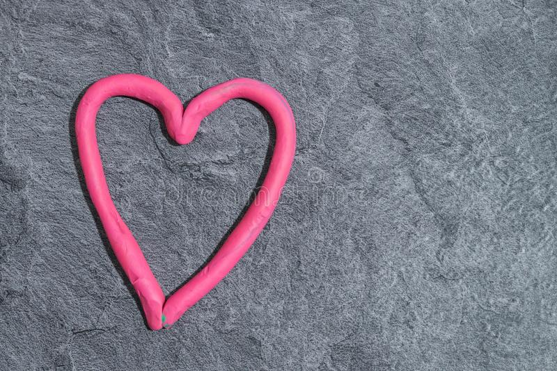 Heart made of play dough in front of grey background.  royalty free stock images