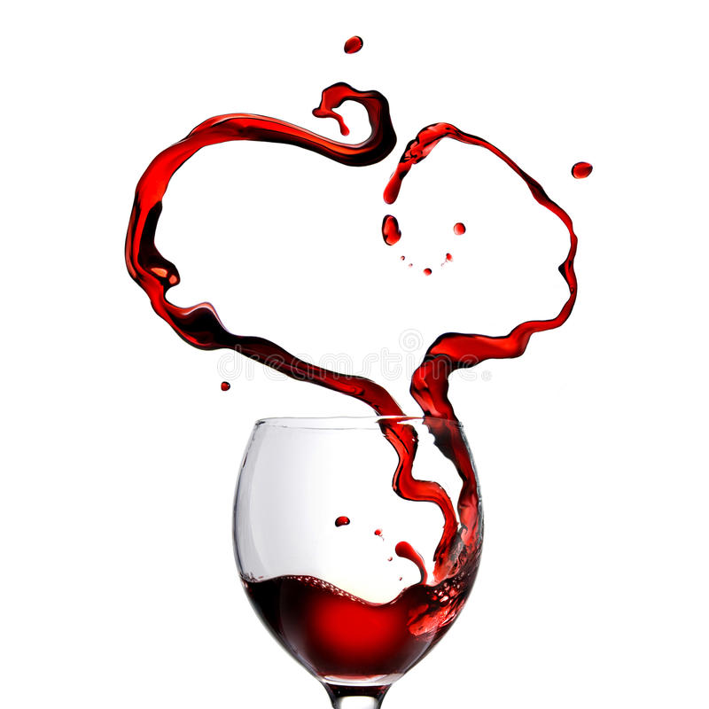 Heart made of pouring red wine in glass. Isolated on white royalty free stock photo