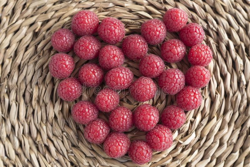 Heart made of raspberries on rustic background royalty free stock image