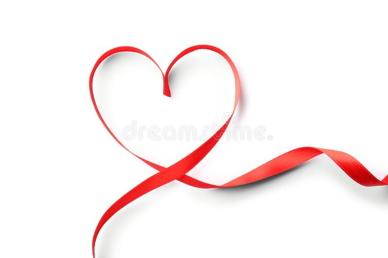 Heart made of red ribbon on white background, top view. Festive royalty free stock image