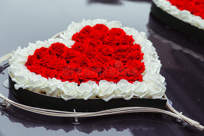 Heart made of red and white roses lies on the black hood stock photography