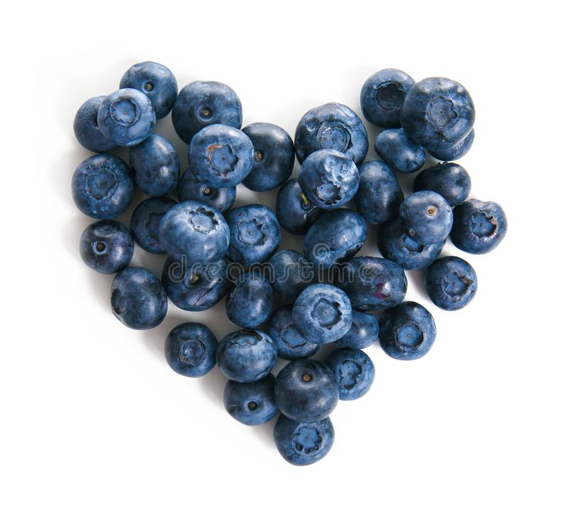 Heart made of ripe blueberries on white background stock image