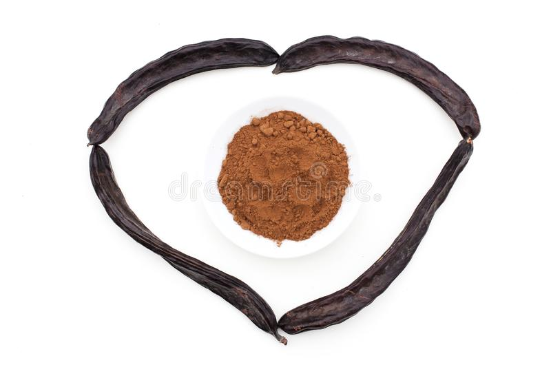 Heart made from ripe carob pods with carob powder in plate inside it. Healthy alternative to cocoa and sugar. Flat lay on white background royalty free stock images