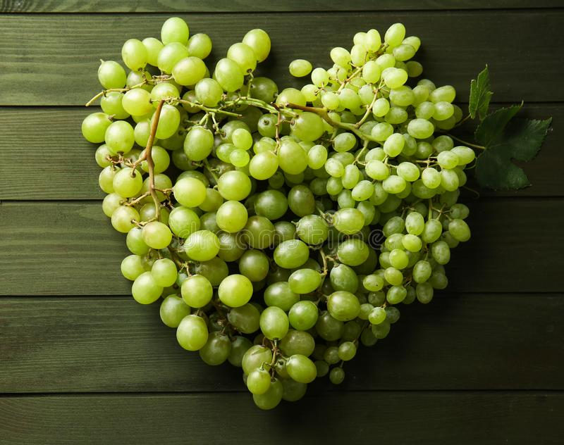 Heart made of ripe sweet grapes on wooden background royalty free stock image