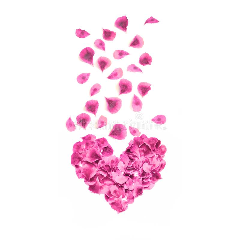 Heart made of rose petals. Red rose petals heart over white background. Top view. Love and romantic theme. royalty free stock photography