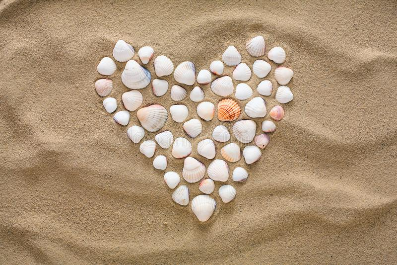 Heart made of sea shells and pebbles. Heart shape made of sea pebbles and shells on sandy ocean beach, top view, copy space. Love summer vacation background stock photos