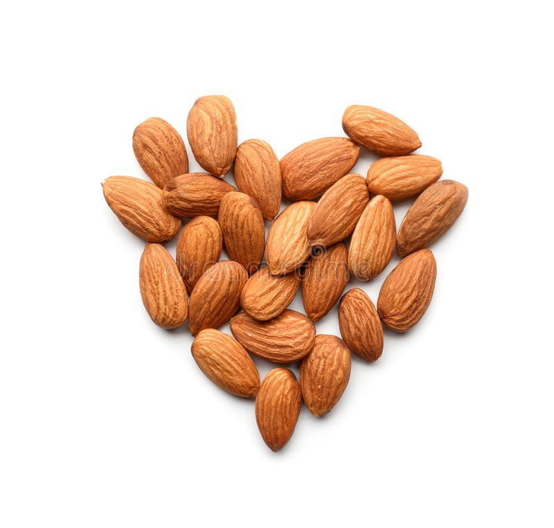 Heart made of tasty almond nuts on white background stock photo