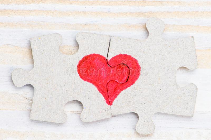 Heart made of two pieces of jigsaw puzzle on light wooden table, close-up royalty free stock photography