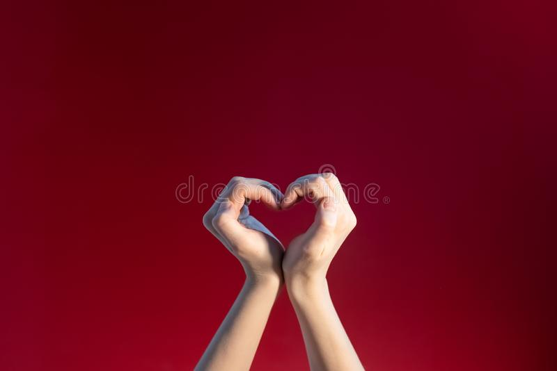 Heart made up of female hands on a red background stock images