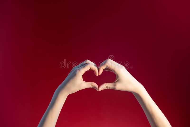 Heart made up of female hands on a red background royalty free stock photography