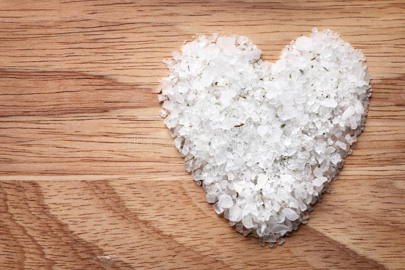 Heart made of white sea salt on wooden background, space for text. Spa treatment. Heart made of white sea salt on wooden background, top view with space for text royalty free stock photography