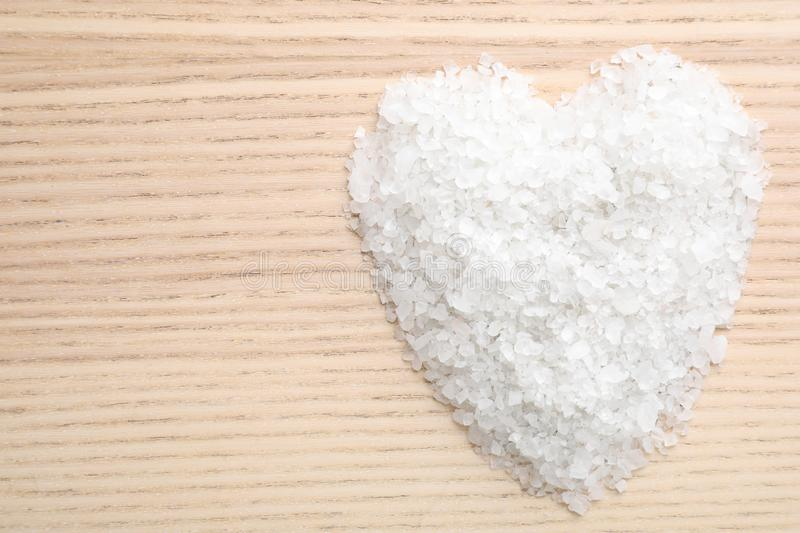Heart made of white sea salt on wooden background, top view. Spa treatment. Heart made of white sea salt on wooden background, top view with space for text. Spa royalty free stock photo