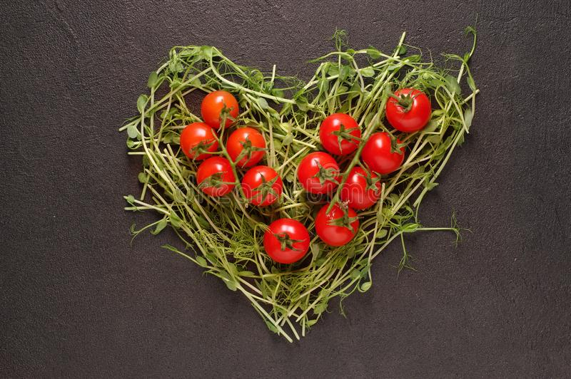 Heart made of young pea shoots and cherry tomatoes on black background; Heart symbol. Vegetables diet concept. Top view, flat lay. Heart made of young pea shoots royalty free stock images