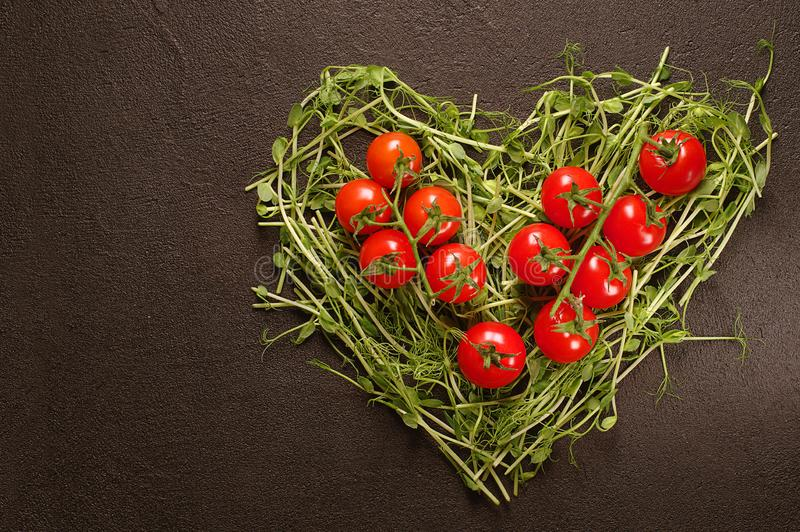 Heart made of young pea shoots and cherry tomatoes on black background; Heart symbol. Vegetables diet concept. Top view, flat lay. Heart made of young pea shoots stock photography