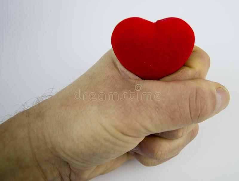 Heart in a man`s fist on a white background, there is free space to fill royalty free stock photography