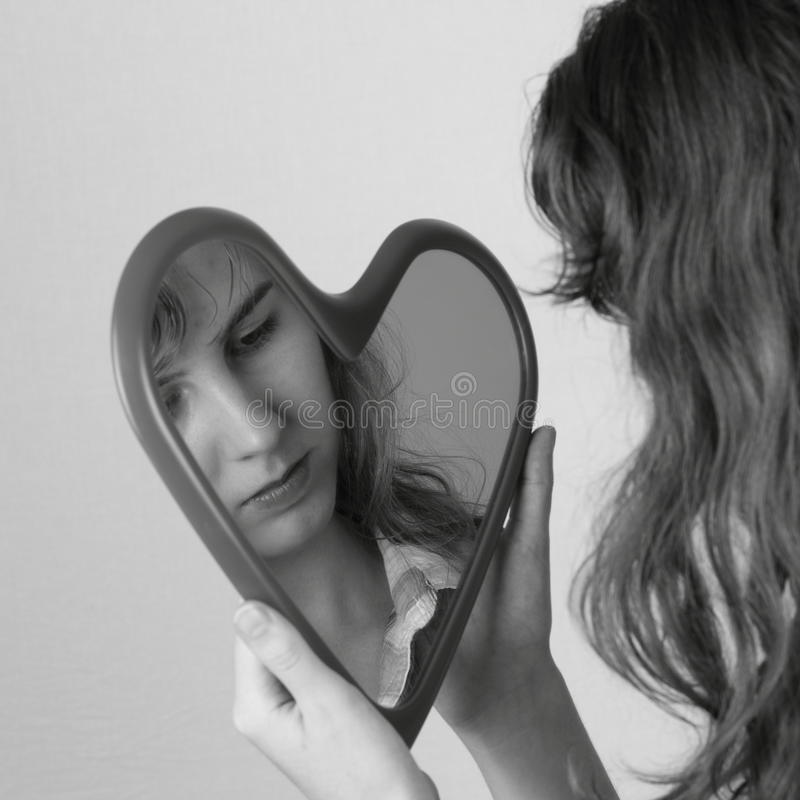 Heart mirror reflecting face of girl. A black-and-white shot of a heart shaped mirror reflecting a young womans face; neutral background stock images