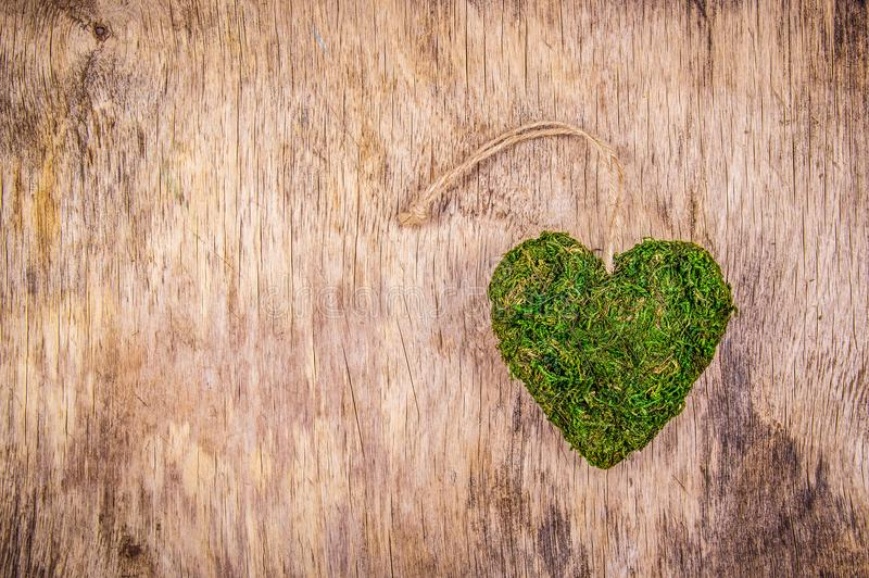 Heart of moss. Green heart on wooden background. Eco style. Eco gift. St. Valentine`s Day. royalty free stock image