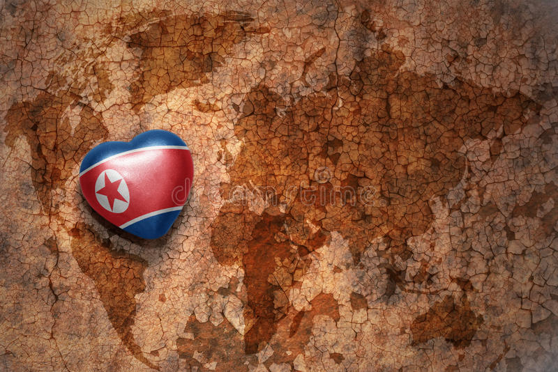 Heart with national flag of north korea on a vintage world map crack paper background. Concept royalty free stock photos