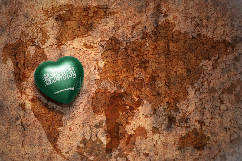 Heart with national flag of saudi arabia on a vintage world map crack paper background. Concept stock photo