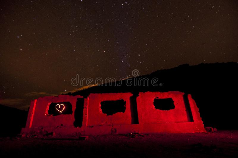 Heart neon light painting in ruins under stars night sky stock photography