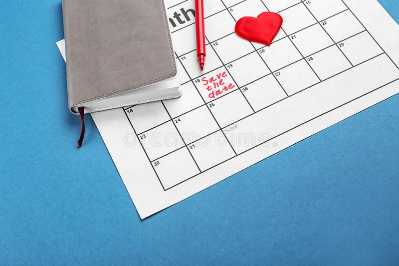 Heart, notebook and calendar with inscription \'Save the Date\' on color background stock photo