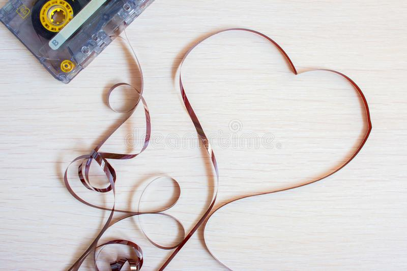 Heart from an old recorder cassette tape on a wooden background.  stock photos
