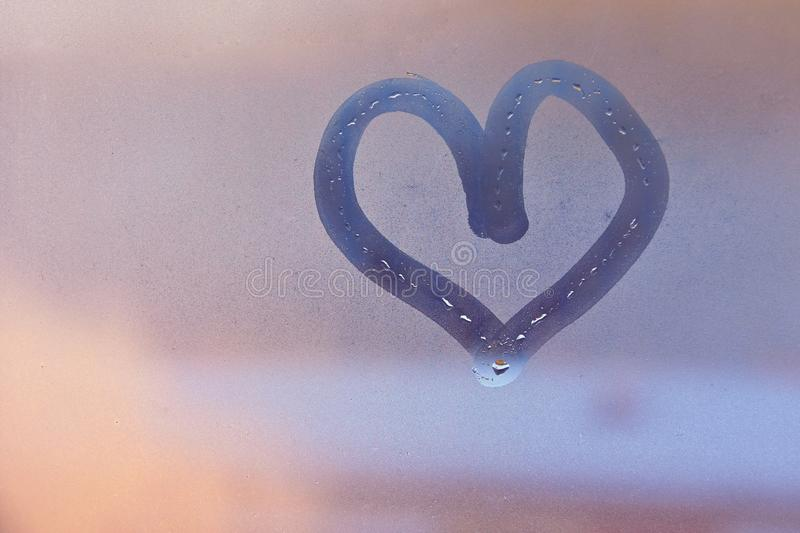 Heart painted with finger on foggy window stock image