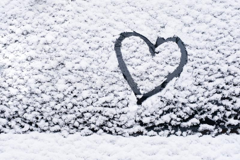 The heart is painted on the glass of the car, on the background of snow. Symbol of love, romance, Valentine`s Day.  royalty free stock images