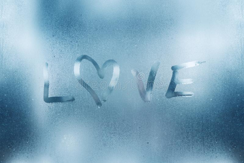 The heart is painted on the misted glass in the winter. stock photos