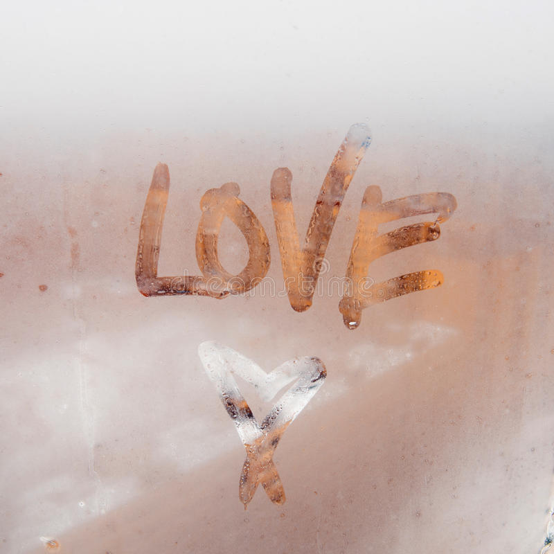 Heart painted on a misted window. Autumn rain, inscription on the sweaty glass - love and heart. stock photography
