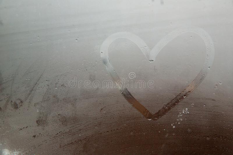 A heart painted on a misted window.Heart on misted glass. Heart on a window background. royalty free stock photo