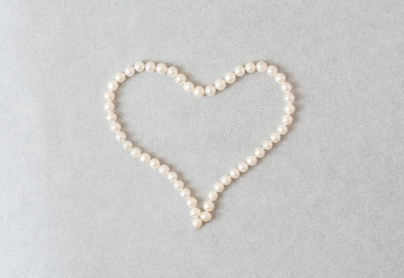 Heart of pearls on a light pearl background royalty free stock photos