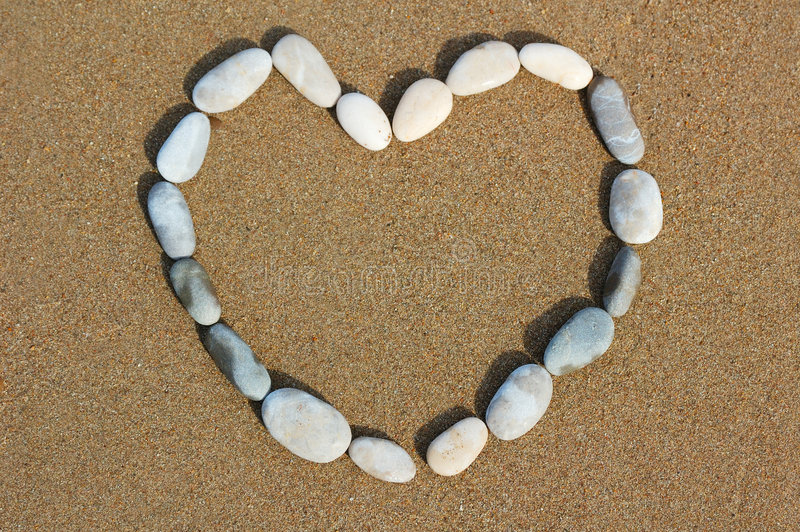 Heart from pebbles on sand. Contour heart from pebbles on sand stock photography