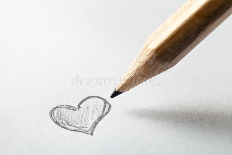 Heart and Pencil. Heart drawn in pencil on a paper sheet, macro shot with copy space royalty free stock photo