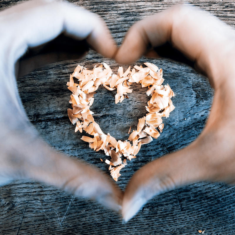 A heart from petals lying on a wooden table and hands. A heart from petals lying on a beautiful old wooden table and heart from woman hands royalty free stock image