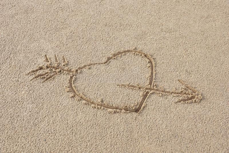 heart pierced by an arrow drawing on the sand beach royalty free stock photography