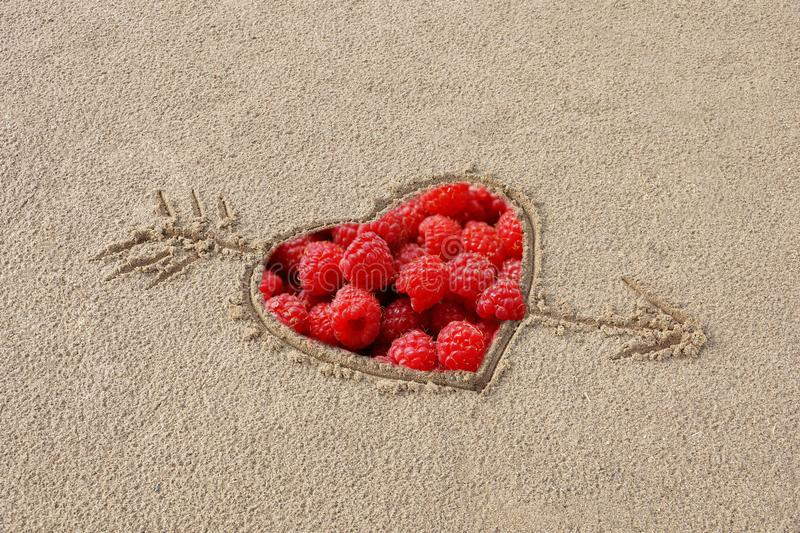 heart pierced by an arrow drawing on the sand beach inside the r stock photos