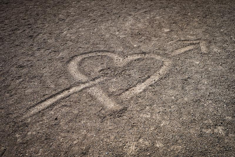 A love heart drawn in the volcanic sand of the mount Teide highland plain. Heart pierced with arrow sketched into the volcanic soil of Tenerife island royalty free stock photo