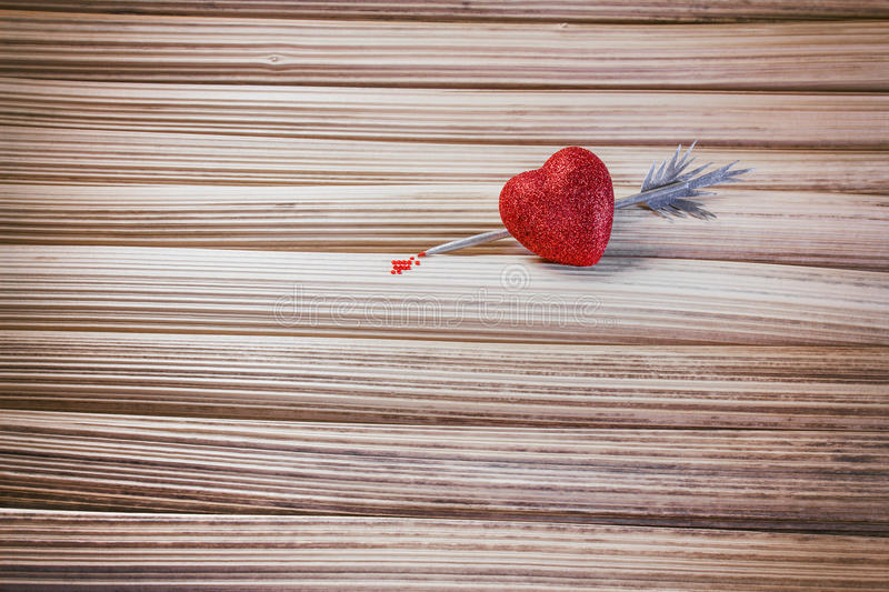 Heart pierced by a silver arrow. Blood dripping from the tip of royalty free stock photo