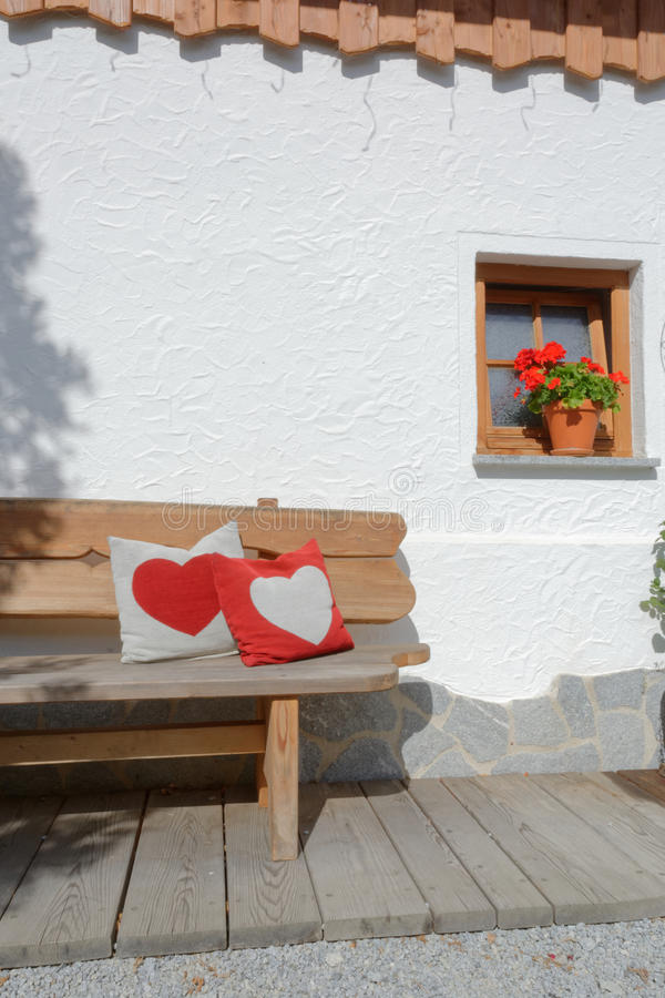 Heart pillows on a garden bench with flowers. Heart pillows on a bench with flowers royalty free stock images